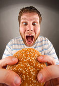 Man eating juicy hamburger — Stock Photo