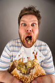 Dirty man chewing hamburger — Stock Photo