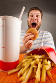 Expressive man eating fast food — Stock Photo