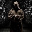 Praying monk in dark temple corridor - Stock Photo