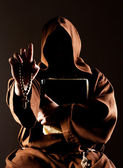 Mystery preaching monk with bible — Stock Photo