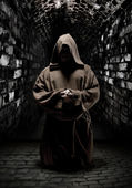 Praying monk in dark temple corridor — Stock Photo