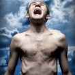 Despaired screaming man against dramatic sky — Stock fotografie