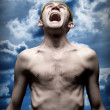Despaired screaming man against dramatic sky — Stockfoto