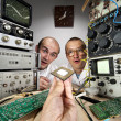 Two funny nerd scientists looking at modern computer processor - Stock Photo