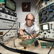 Funny nerd scientist soldering at vintage laboratory — Stock Photo #6072526