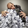 Exhausted depressive businessman laying on crumpled papers - Стоковая фотография