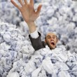 Businessman sinking in big heap of crumpled papers — Stock Photo