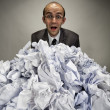 Surprised businessman reaches out from crumpled papers — ストック写真
