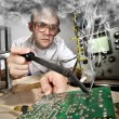 Funny nerd scientist soldering at vintage laboratory - Stock Photo