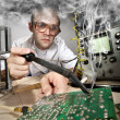 Funny nerd scientist soldering at vintage laboratory - Stockfoto