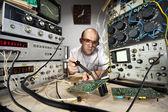 Funny nerd scientist soldering at vintage laboratory — Stock Photo