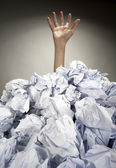 Hand reaches out from heap of papers — Stock Photo