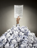Hand with agreement reaches out from heap of papers — Stock Photo