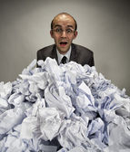 Surprised businessman reaches out from crumpled papers — Stock Photo