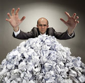 Serious businessman reaches out from crumpled papers — Stock Photo