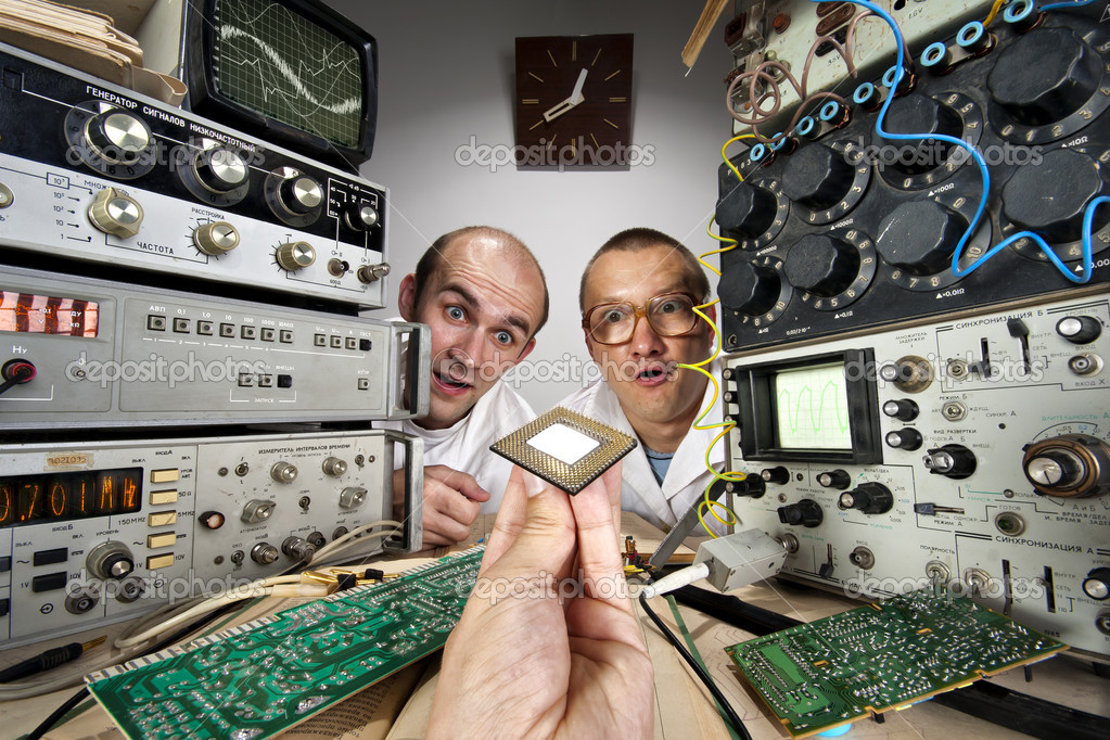 Two funny nerd scientists at vintage technological laboratory looking at modern computer processor — Stock Photo #6072522