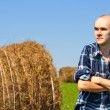 Farmer in field against wheat bales — Stock Photo