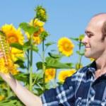 Farmer holding bottle of sunflowers oil — Stock Photo