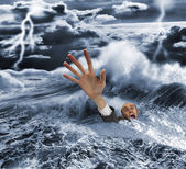 Businessman sinking in dark stormy sea — Stock Photo