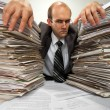 Businessman with big piles of paperwork — Stockfoto
