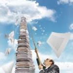 Businessman climbing up the pile of paperwork — Stock Photo