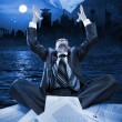 Businessman throwing papers at night — Stock Photo