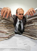 Businessman with big piles of paperwork — Stock Photo