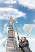 Businessman climbing up the pile of paperwork — Stock Photo
