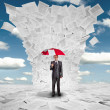 Businessman with red umbrella under huge wave of documents — Stockfoto