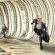 Businessmen running in dollar tunnel — Stock Photo #6639845