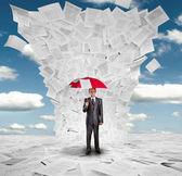 Zakenman met rode paraplu onder enorme golf van documenten — Stockfoto