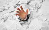 Hand reaches out from crumpled papers — Stock Photo
