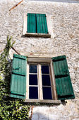 Old facade with windows with green shutters — Stock Photo