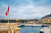 The flag of Monaco and Monte Carlo harbor in the background — Stock Photo