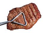 Kleště drží grilovaný hovězí steak ze svíčkové panenka — Stock fotografie