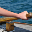 Hand on Tiller Steering a Schooner Sailboat - Stock Photo