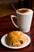 Cappuchino and pain au chocolat. — Stock Photo