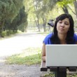 Woman with laptop in park — Stockfoto