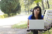Woman with laptop in park — ストック写真