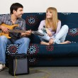 Stock Photo: Young couple having rest with a music