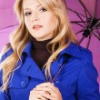 Pretty woman in blue coat with umbrella — Stock Photo