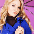 Pretty model in blue coat with an umbrella — Stock Photo #5726426
