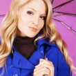 Royalty-Free Stock Photo: Pretty model in blue coat with an umbrella