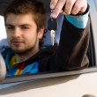 Man holding out car keys - Stock Photo