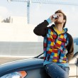 Car driver with a refreshing drink - Stock Photo