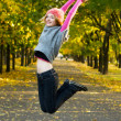 Stock Photo: Joyful young woman jumping in the park