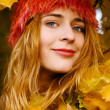 Beautiful young woman among yellow leaves — Stock Photo #5727209