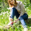 Beautiful young woman sitting in dandelions — ストック写真 #5727213