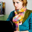 Pretty young woman working at laptop — Stock Photo